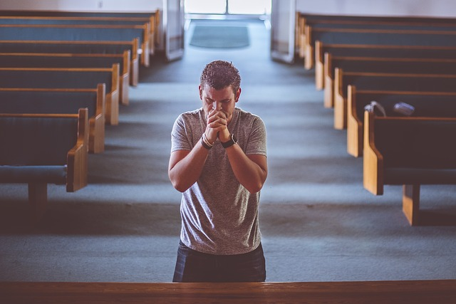 A man in church, on his knees, praying